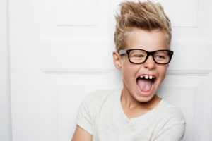 Boy wearing glasses who has adult teeth that are gappy.